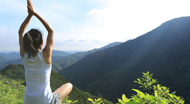woman on mountain peak practicing yoga