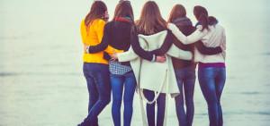 group of girls hugging on beach